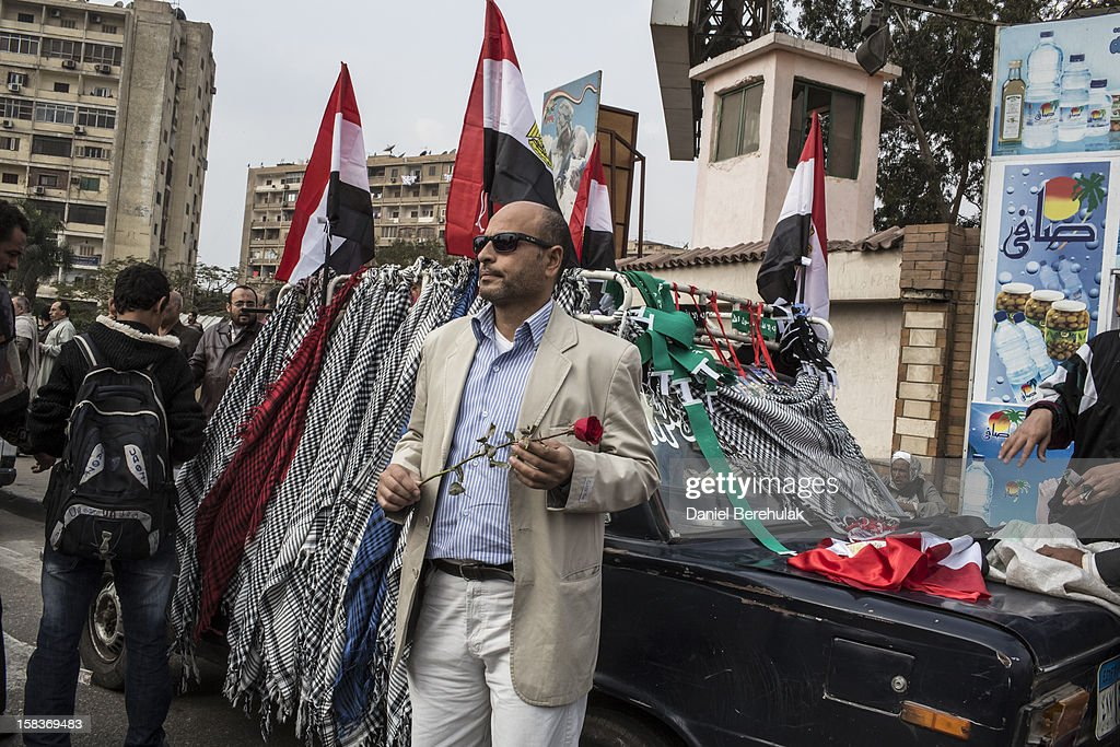 A man holds a rose as he watches supporters of Egyptian President Mohamed Morsi and members of the Muslim Brotherhood chant slogans on December 14, 2012 in Cairo, Egypt. Opponents and supporters of Egyptian President Mohamed Morsi staged final rallies in Cairo ahead of tomorrow's referendum vote on the country's draft constitution that was rushed through parliament in an overnight session on November 29. The country's new draft constitution, passed by a constitutional assembly dominated by Islamists, will go to a referendum vote on December 15.