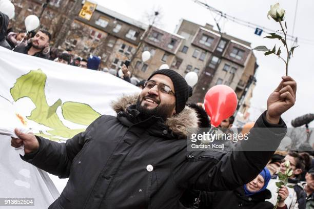 A man holds a rose as refugees and supportive locals march under the motto 'Live Without Hate' in the city center to protest for peaceful coexistence...
