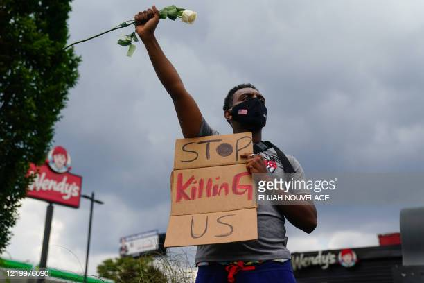 TOPSHOT A man holds a sign and a white rose in his fist while facing traffic outside a burned Wendys restaurant on the second day following the...