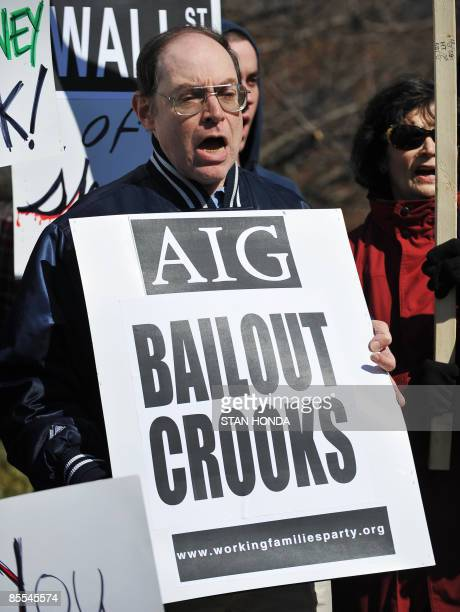 A man holds a sign as he gathers with other protesters outside the headquarters of AIG Financial Products March 21 2009 in Wilton Connecticut A bus...