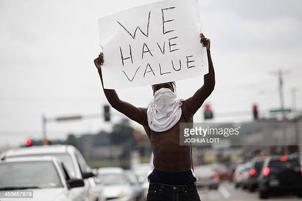 A man holds a sign as he protest on August 15 the shooting death of 18yearold Michael Brown in Ferguson Missouri US authorities on Friday identified...