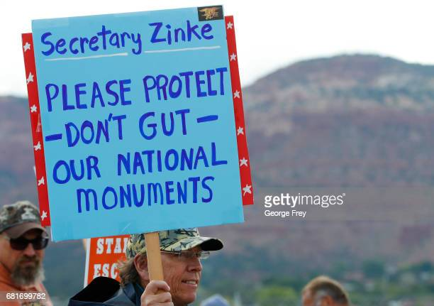 A man holds a sign as he waits at the Kanab Airport to protest US Secretary of the Interior Ryan Zinke on May 10 2017 in Kanab Utah Zinke has been in...
