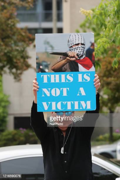 Man holds a sign as members of the Jewish Defence League and the Northern Guard hold a pro-Israel counter protest during the Al Quds Day rally...