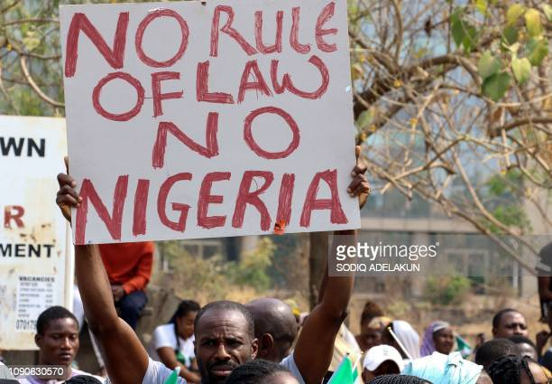 A man holds a sign as protesters assemble outside the secretariat of the Nigerian Bar Association during a protest in Abuja over the suspension of...