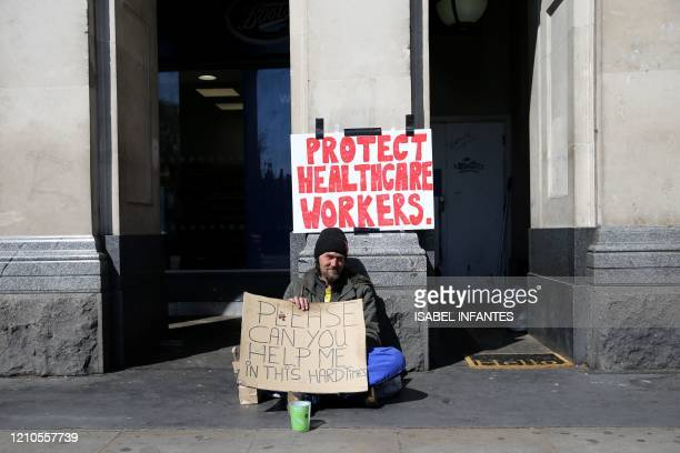 TOPSHOT A man holds a sign asking for help as he sits on the pavement in Westminster central London on April 21 during the nationwide lockdown to...