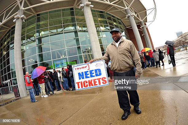 A man holds a sign concerning tickets as fans arrive early at the entrance gates prior to a game between the Connecticut Huskies and the South...