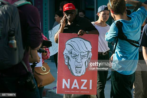 A man holds a sign declaring Republican presidential candidate Donald Trump a Nazi outside a campaign rally on June 2 2016 in San Jose California The...