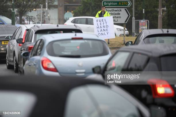 Man holds a sign directing the heavy traffic queues outside a busy petrol station on September 25, 2021 in Brighton, England. BP and Esso have...