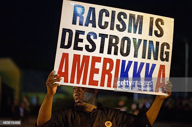 A man holds a sign during a civil disobedience action on West Florissant Avenue in Ferguson Missouri on August 10 2015 US police made numerous...