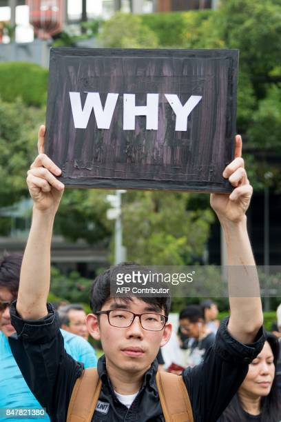 A man holds a sign during a protest against the walkover victory of Halimah Yacob as Singapore's President at Hong Lim Park in Singapore on September...