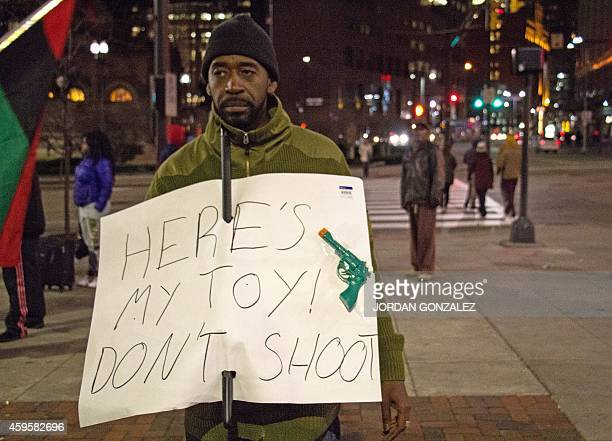 A man holds a sign in Cleveland November 25 2014 referring to the fatal shooting November 23 of Tamir Rice a 12yearold boy who was wielding a replica...