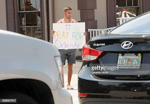 A man holds a sign in support of the victims of the terror attack at gay nightclub Pulse on June 12 2016 in Orlando Florida The suspected shooter...