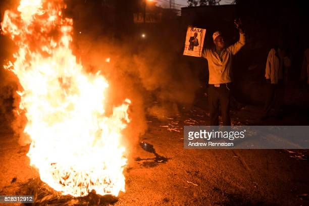 A man holds a sign of opposition candidate Raila Odinga during a protest in Kibera Kenya's biggest slum on August 9 2017 in Nairobi Kenya The protest...