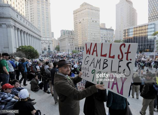 Man holds a sign on the steps of the Federal Courthouse as members of trade unions join Occupy Wall Street protesters as they rally in Foley Square...