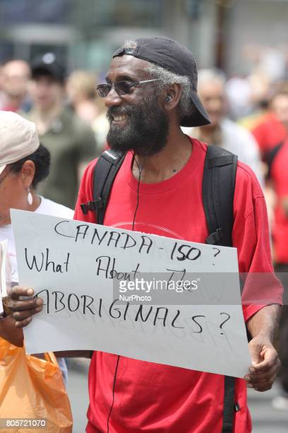Man holds a sign protesting Canada Day and the 150th anniversary of confederation as part of a national day of action called UNsettling Canada 150...