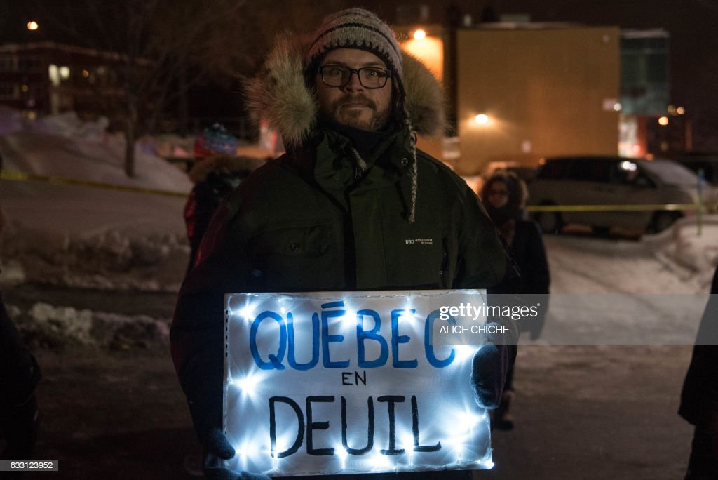 TOPSHOT - A man holds a sign 'Quebec mourning' during a rally near the Islamic Cultural Center in Quebec City, Canada on January 30, 2017. Gunmen stormed into a Quebec mosque during evening prayers January 29 and opened fire on dozens of worshippers, killing six and wounding eight in what Canadian Prime Minister Justin Trudeau condemned as a 'terrorist attack.' Canadian police sought Monday to piece together the motive for a shooting attack, one of the worst attacks ever to target Muslims in a western country. / AFP / Alice Chiche