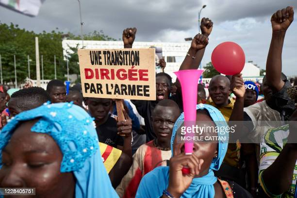 TOPSHOT A man holds a sign reading A transition led by the army as supporters of the CNSP take part in a rally on Independence square in Bamako on...