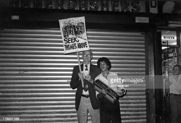 A man holds a sign reading 'Christ is Risen Seek Things Above' whilst another man holds a portable stereo outside a shop in Midtown Manhattan New...