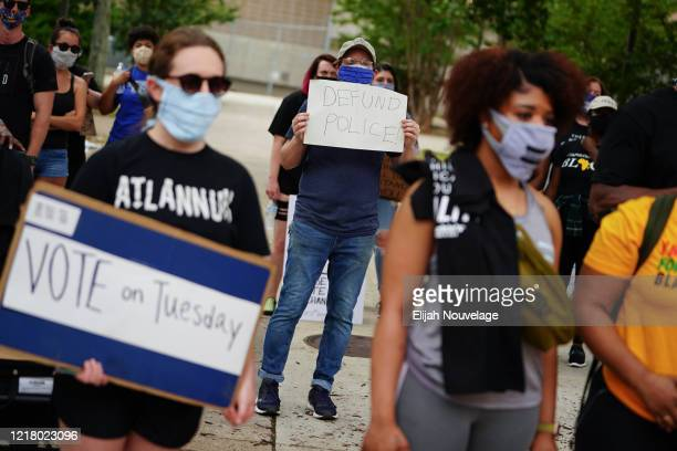 """Man holds a sign reading """"Defund Police"""" during a protest against police brutality on June 6, 2020 in Atlanta, Georgia. This is the 12th day of..."""