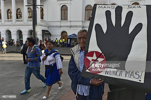 A man holds a sign reading 'Dirty hand never again' during a protest against US multinational energy corporation Chevron at a square in downtown...