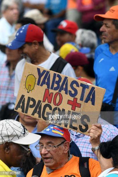 A man holds a sign reading Enough of blackouts before a session of the oppositionled National Assembly at Alfredo Sadel square in Caracas on July 23...