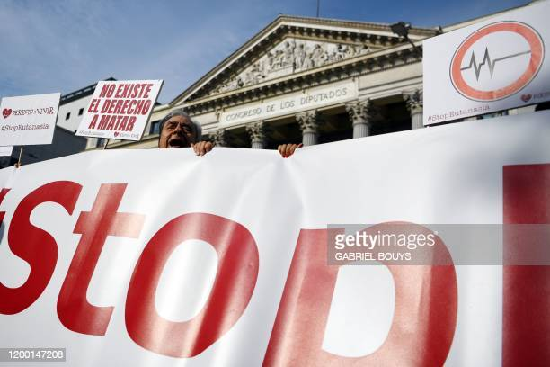 """Man holds a sign reading in Spanish """"There is no right to kill"""" during a demonstration against euthanasia called by """"Derecho a Vivir"""" group in front..."""