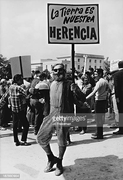 A man holds a sign reading 'La Tierra Es Nuestra' at the 'Solidarity Day' march during the Poor People's Campaign an organised demonstration hoping...