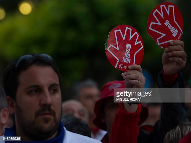 A man holds a sign reading 'NO is no' as he protests with thousands against the growing number of sexual assaults during the San Fermin bull run...