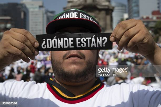 A man holds a sign reading Where are they during a march to demand the Mexican government answers about their loved ones whereabouts as part of the...