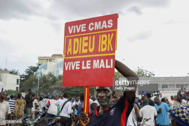 A man holds a sign saying goodbye to IBK referring to Malian President Ibrahim Boubacar Keita as soldiers parade in vehicles along the Boulevard de...