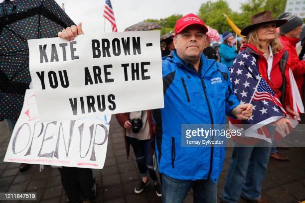 A man holds a sign saying Kate Brown you are the virus at the ReOpen Oregon Rally on May 2 2020 in Salem Oregon Demonstrators gathered at the state...