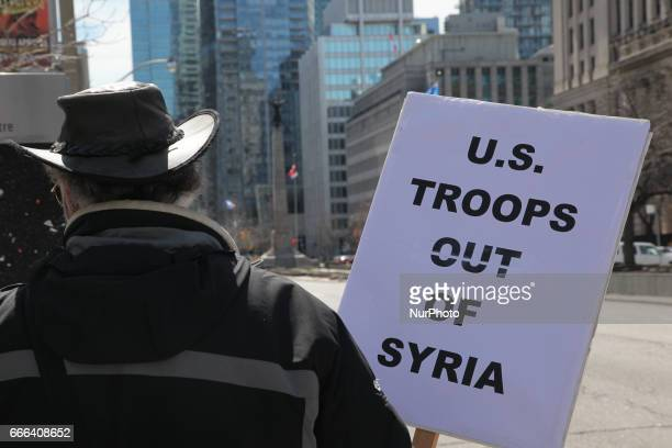 Man holds a sign saying 'US Troops out of Syria' during a protest against US President Donald Trump's decision to launch airstrikes against Syria on...