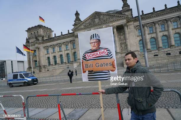 """Man holds a sign showing billionaire and philanthropist Bill Gates in a prisoner's uniform that reads: """"guilty"""" at a rally of supporters of the..."""