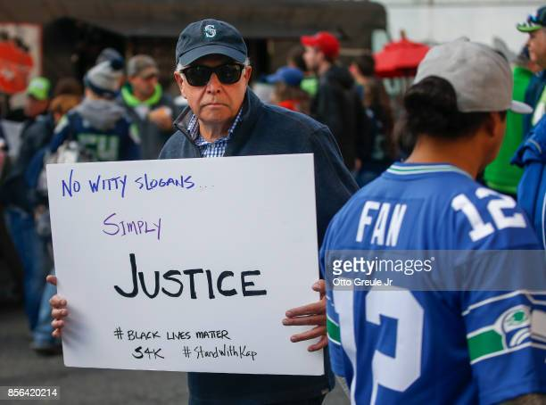A man holds a sign supporting Black Lives Matter and Colin Kaepernick before the game between the Seattle Seahawks and the Indianapolis Colts outside...