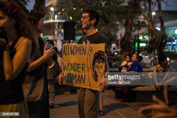 A man holds a sign that reads all women are wonder woman at Tha Pae Gate during the annual International Women's Day event on March 8 2018 in Chiang...