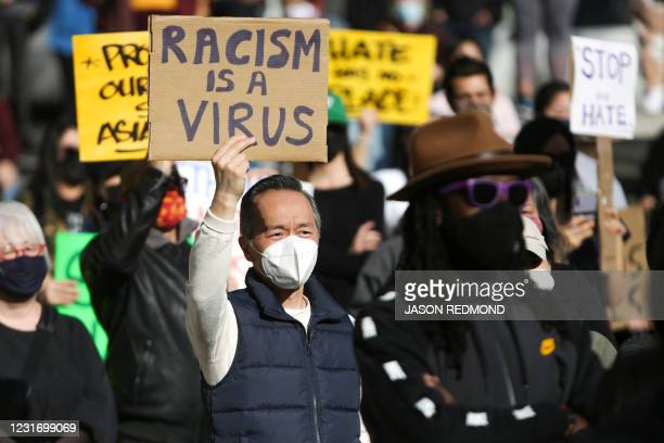 "Man holds a sign that reads ""Racism is a Virus"" during the ""We Are Not Silent"" rally against anti-Asian hate in response to recent anti-Asian crime..."