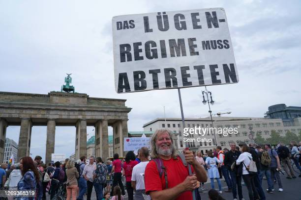 A man holds a sign that reads The lies regime must step down at a gathering of coronavirus skeptics in front of the Brandenburg Gate on the eve of a...
