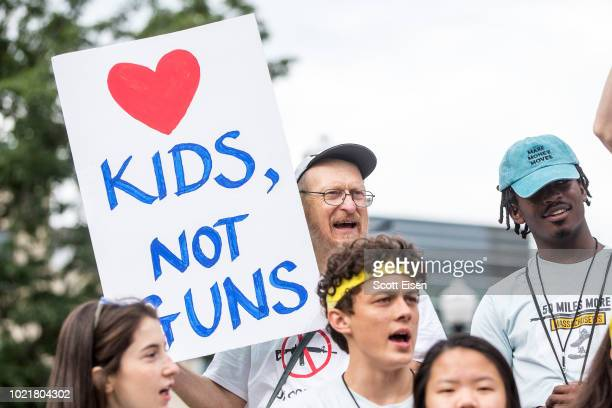 A man holds a sign that say Love Kids Not Guns during the 50 Miles More walk against gun violence which will end with a protest at the Smith and...