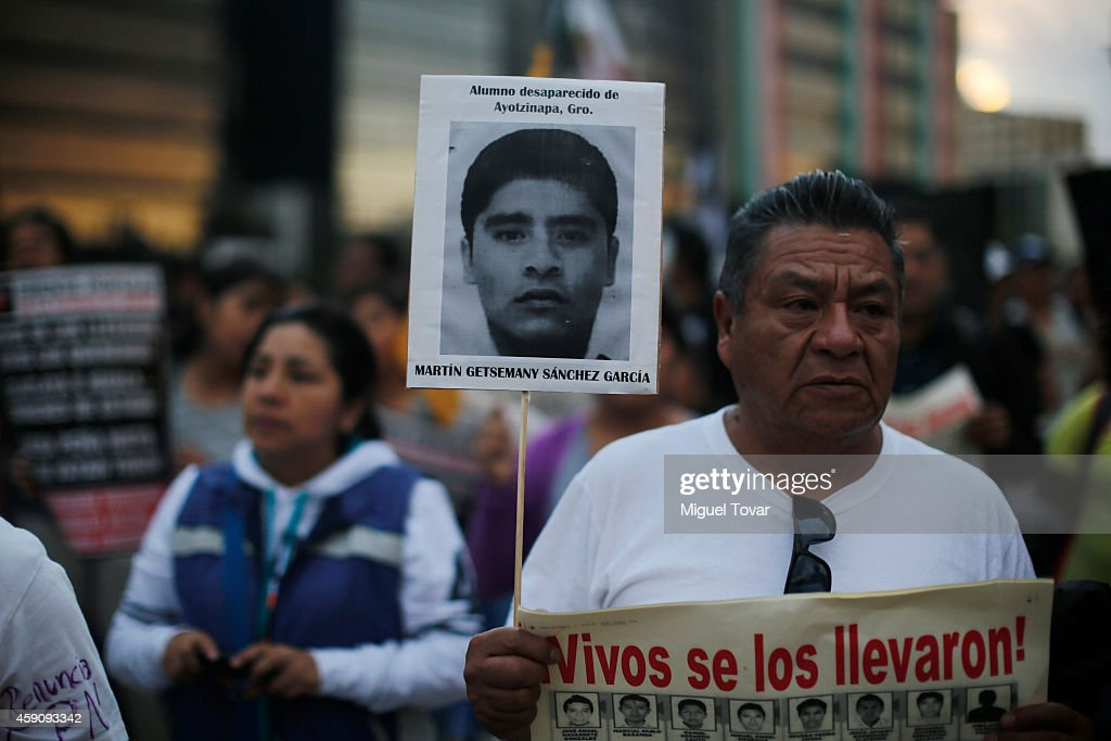 A man holds a sign with the face of one of the missing students of Ayotzinapa during a demonstration against Mexico's government who suggests that 43 missing students were murdered and their charred remains tipped in a rubbish dump and a river in Guerrero, Mexico, on November 16, 2014 in Mexico City, Mexico.