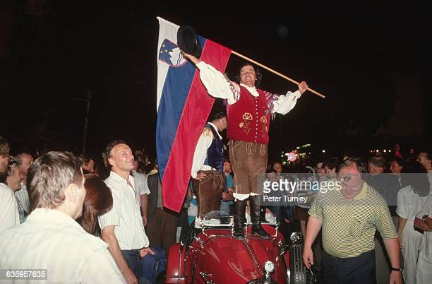 A man holds a Slovenian flag as he stands on a vehicle to celebrate the Slovenian Independence Movement