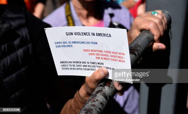 A man holds a small sign referring to gun violence in America during a 'March For Our Lives' rally in Santa Fe New Mexico The rally and march part of...