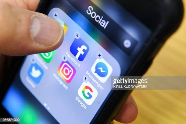 A man holds a smart phone with the icons for the social networking apps Facebook Instagram and Twitter seen on the screen in Moscow on March 23 2018...