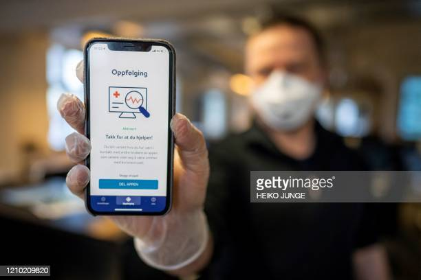A man holds a smartphone showing a tracking and tracing app launched by the National Institute of Public Health to try to halt a return of the new...