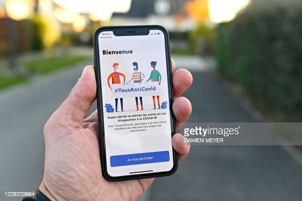 """Man holds a smartphone showing the new """"TousAntiCovid"""" application in Rennes, western France, on October 22 as several departments were put in..."""