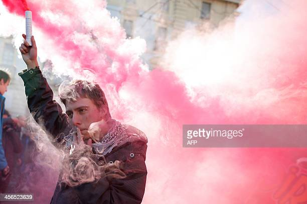 Man holds a smoke bomb during a protest by students against the local government in downtown Turin on December 14, 2013. Protesters clashed with...