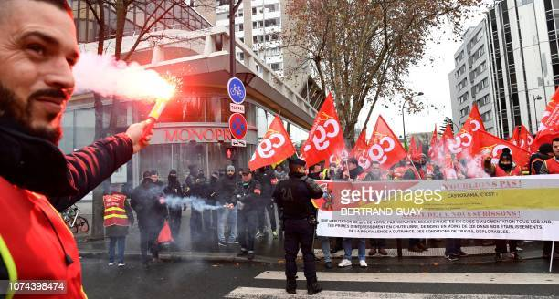A man holds a smoke bomba while people wave the General Confederation of Labour trade union's flag and chant slogans as they take part in a rally in...