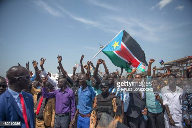 Man holds a South Sudanese flag as people wave to greet the South Sudanese president in the John Garang Mausoleum grounds in Juba on July 9, 2015...
