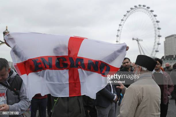 A man holds a St George's Cross flag with 'England' written on it on Westminster Bridge as people attend a vigil to remember the victims of last...