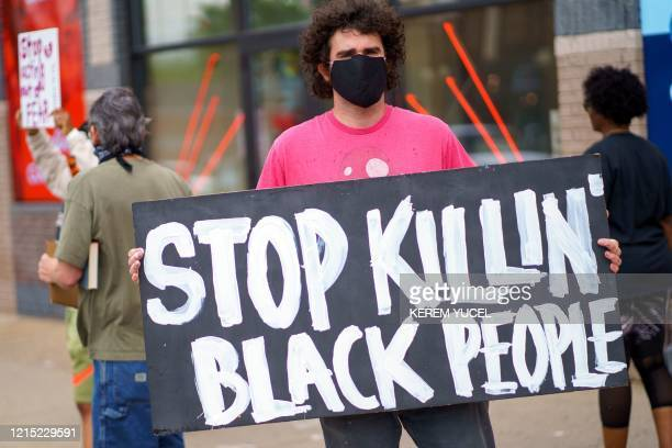 A man holds a 'Stop Killing Black People placard while protesting near the area where a Minneapolis Police Department officer allegedly killed George...