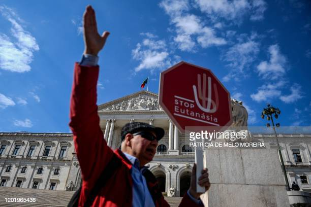 """Man holds a stop sign reading """"Stop Euthanasia"""" during a protest against the decriminalization of euthanasia in front of the parliament on February..."""
